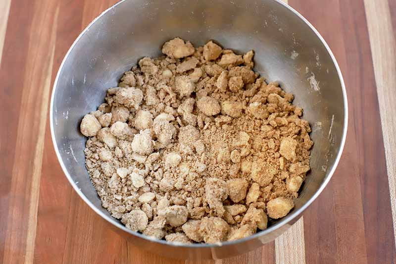 A brown sugar and butter streusel mixture with round clumps and light brown powdery bits is at the bottom of a stainless steel mixing bowl, on a wood surface.