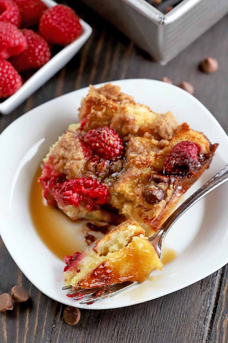 A forkful of French toast casserole is on the edge of a white plate in the foreground, with the remainder of the portion in a pool of maple syrup behind it, on a dark brown wood surface, with scattered chocolate chips, a small, square, white ceramic dish of fresh raspberries, and the corner of a metal baking pan.