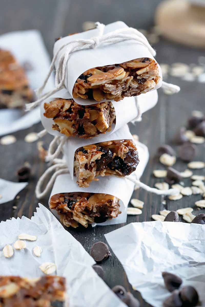 Vertical image of a stack of four homemade granola bars wrapped in paper and tied with string, on a dark brown wood surface with more bars on rectangular pieces of parchment paper, with scattered oats and chocolate chips.