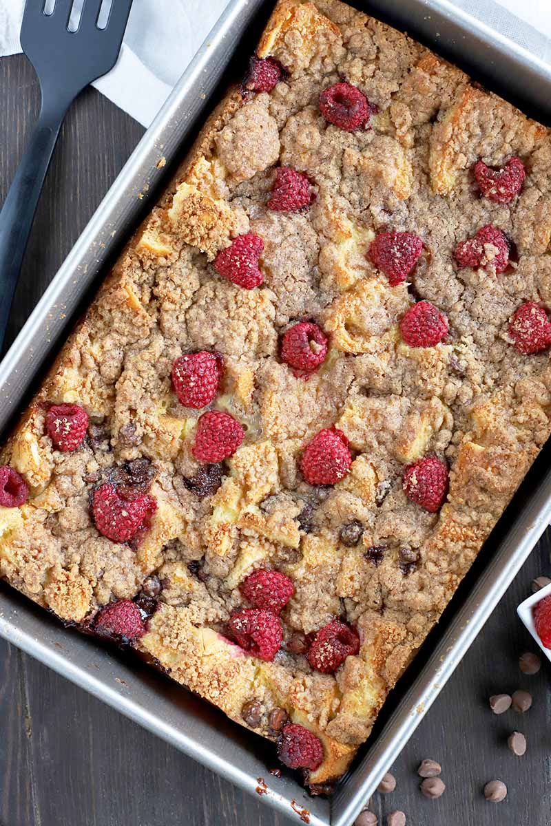 Overhead shot of a metal baking pan filled with a just-baked French toast casserole arranged at an angle, on a dark brown wood surface with a black plastic spatula for serving, a white cloth, and scattered chocolate chips.