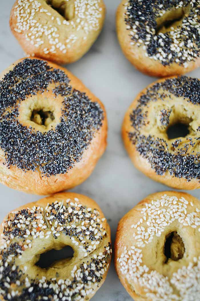 Closeup top-down view of a batch of homemade einkorn flour bagels with various toppings.
