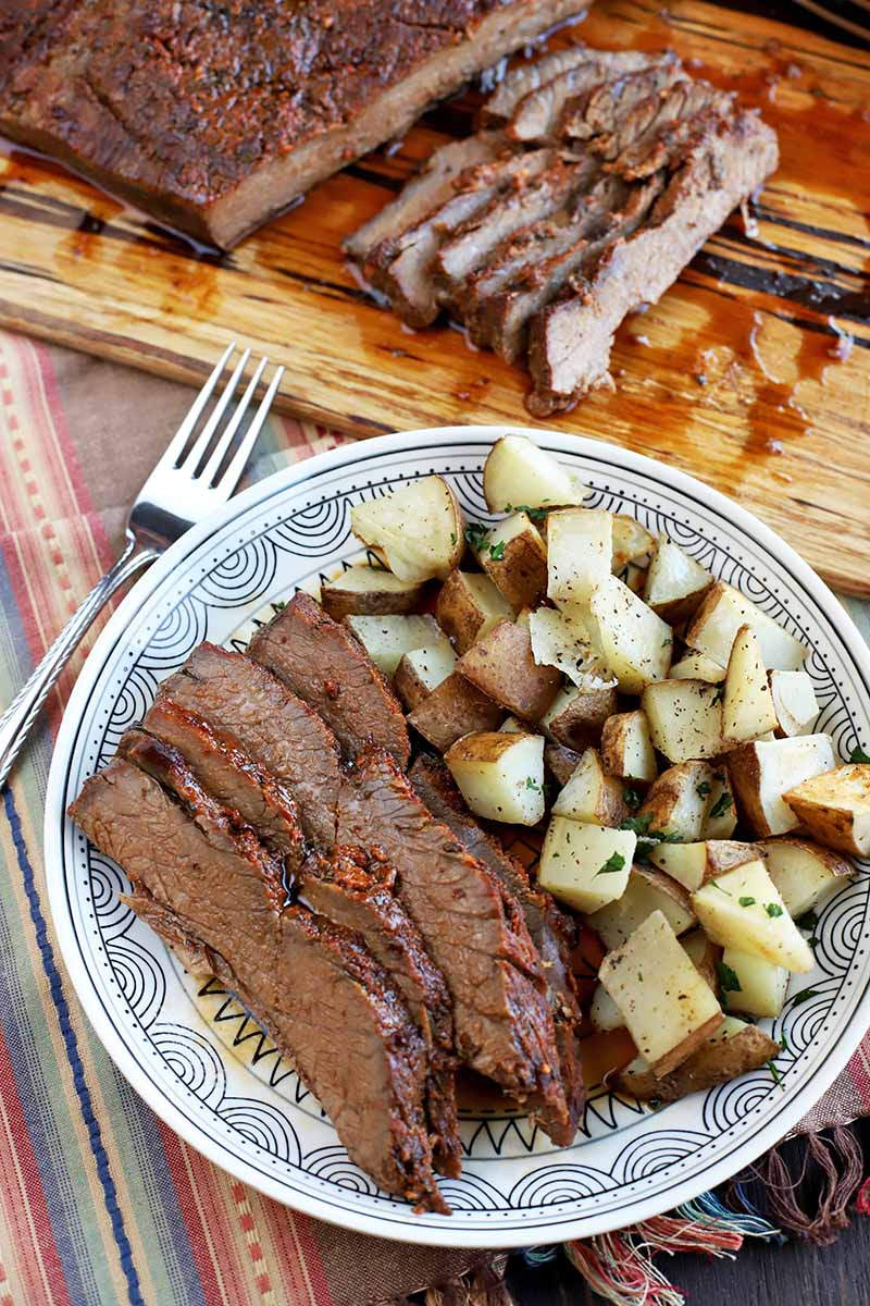 Vertical image of a black and white patterned plate of sliced roast beef brisket and herb roasted potatoes, with a fork on a striped cloth in muted colors, with a wooden board topped with more of the meat dish in the background.