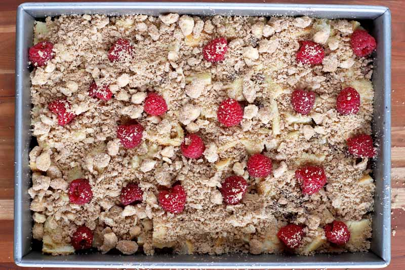 Overhead horizontal shot of a French toast casserole in a metal baking pan that is ready to go into the oven, topped with fresh raspberries and a brown sugar crumble mixture, on a wood surface.