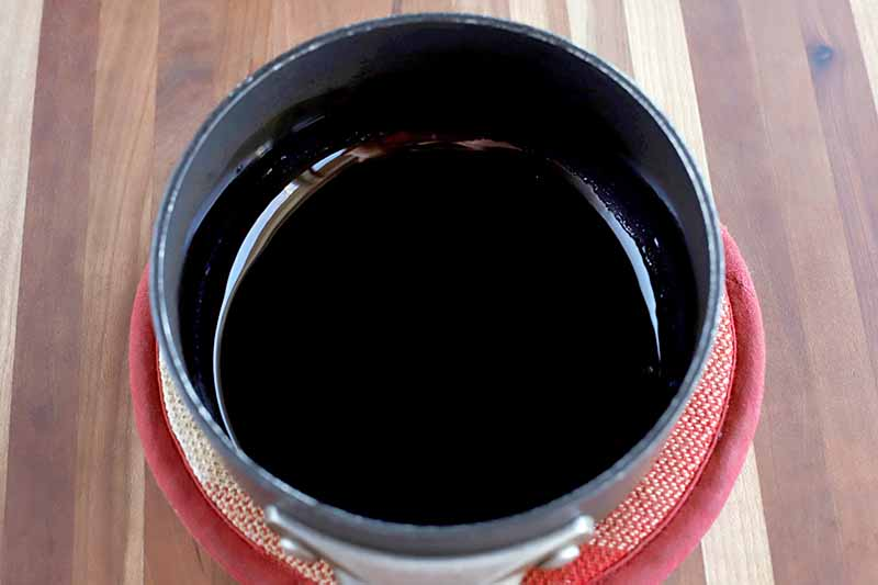 Overhead horizontal shot of a nonstick saucepan of balsamic reduction sauce on a round red potholder, on a brown wood table.