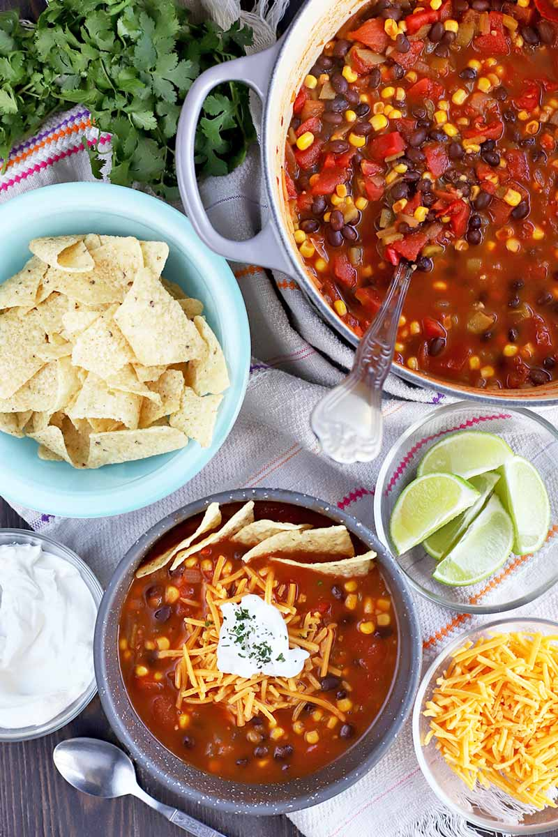 Overhead vertical shot of a large enameled cast iron cooking pot and a gray bowl of vegetarian taco soup with a light blue bowl of corn chips, smaller glass bowls of lime wedges, shredded cheddar cheese, and sour cream, a bunch of fresh cilantro, and a spoon, on a white striped cloth on top of a dark brown wood table.
