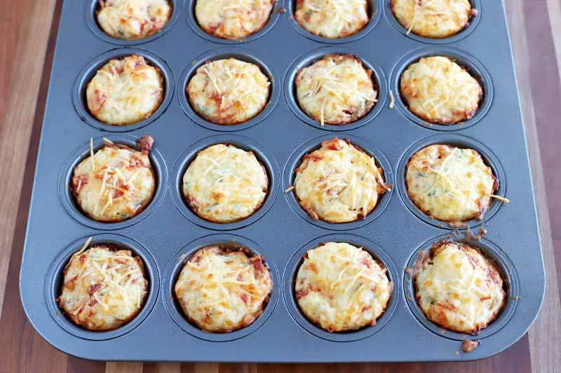 HOrizontal shot of a muffin pan filled with mini pizza bites with melted cheese on top, on a light brown background.