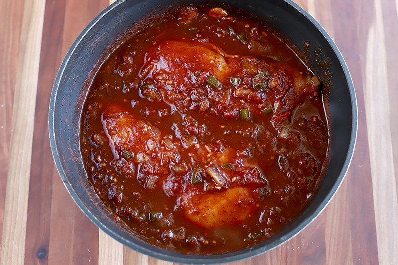 Horizontal image of chicken breasts in a red sauce in a pot.