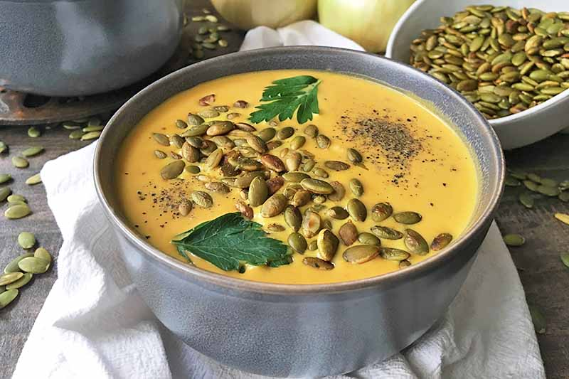 Horizontal image of a gray bowl with orange soup with garnishes, surrounded by onions and toasted pumpkin seeds.