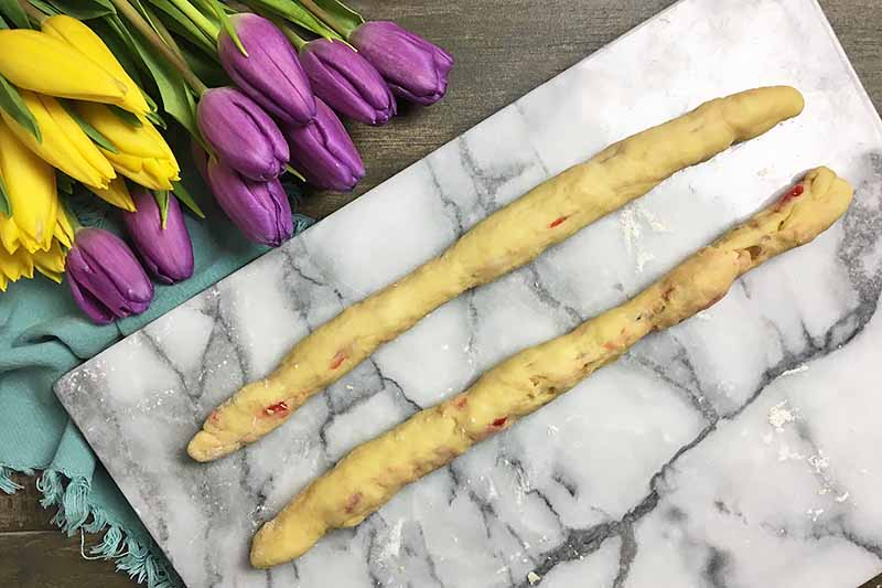Horizontal image of two dough ropes on a marble counter next to flowers.