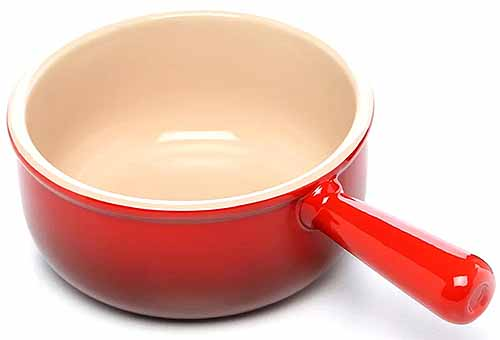 Le Creuset stoneware French onion soup crock in cerise with cream-colored glazed interior, isolated on a white background.
