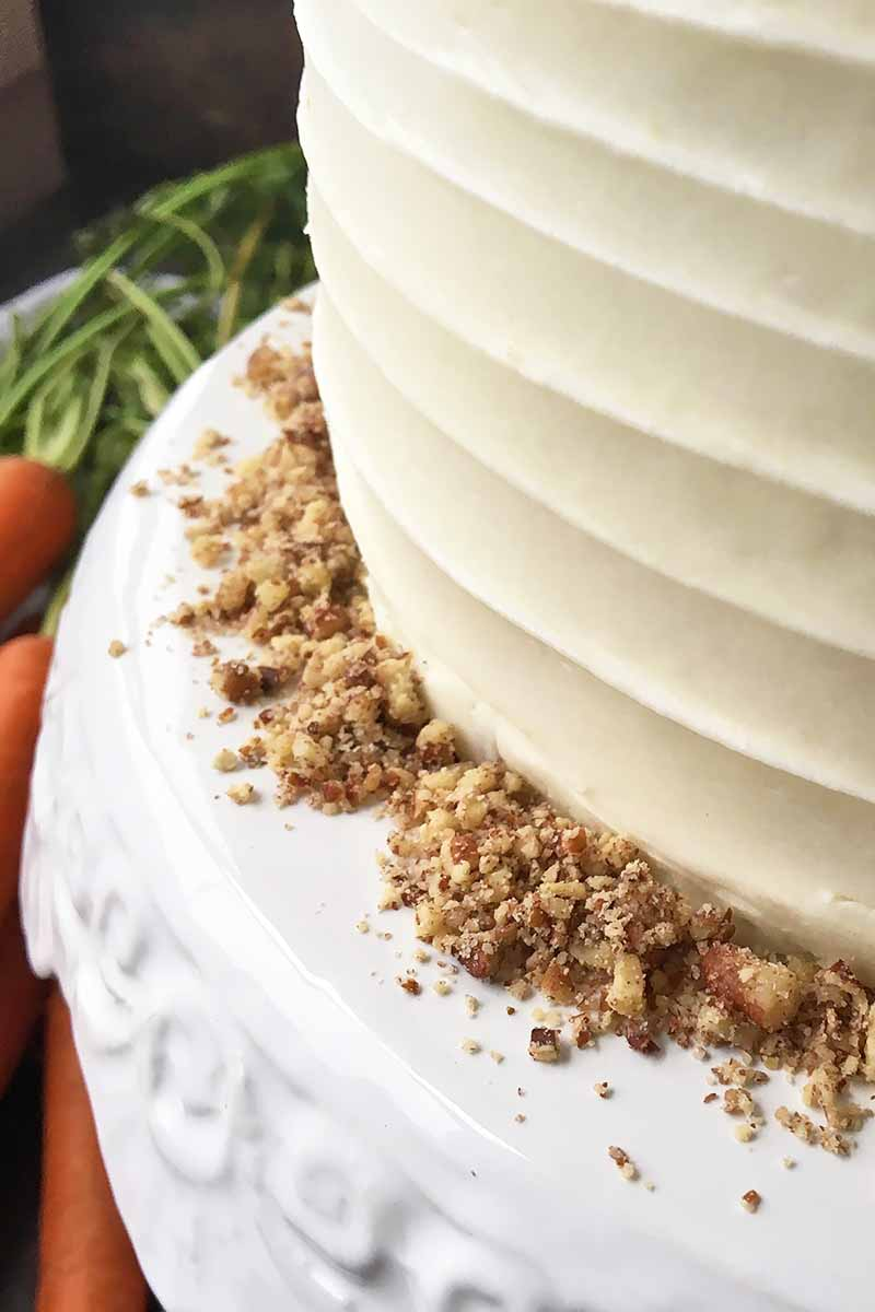 Vertical close-up image of the side of a decorated dessert with ground nuts on a white stand.