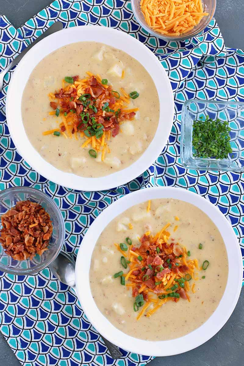 Vertical overhead shot of two white bowls of loaded baked potato soup topped with shredded cheese, crumbled bacon, and chopped chives and scallions, surrounded by small bowls of more of the garnishes, on a light and dark blue patterned cloth on top of a slate surface.