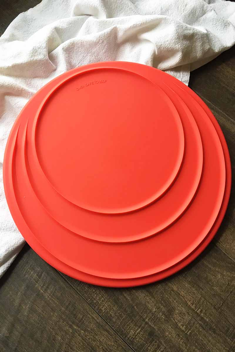 Vertical image of a red lid with three circles in it on a white towel.