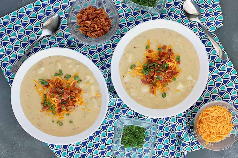 Overhead horizontal shot of two white bowls of loaded baked potato soup surrounded by small dishes of crumbled bacon, shredded cheddar cheese, and chopped chives, with two spoons on a light and dark blue patterned cloth, on a gray slate surface.