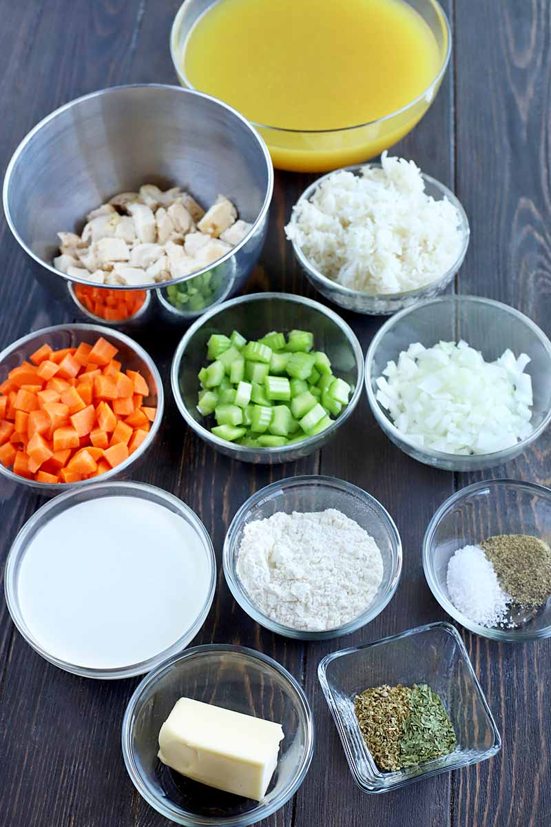 Vertical oblique overhead shot of eleven small and medium-sized glass and stainless steel bowls and square dishes of chicken broth, chopped cooked poultry, onions, celery, carrots, flour, cream, rice, salt, pepper, butter, and herbs.