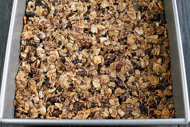 Closeup of a baked mixture of oats, fruit, nuts, and chocolate in a metal baking pan, on a dark brown wood surface.
