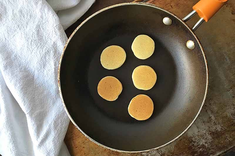 Horizontal image of mini pancakes in a skillet.