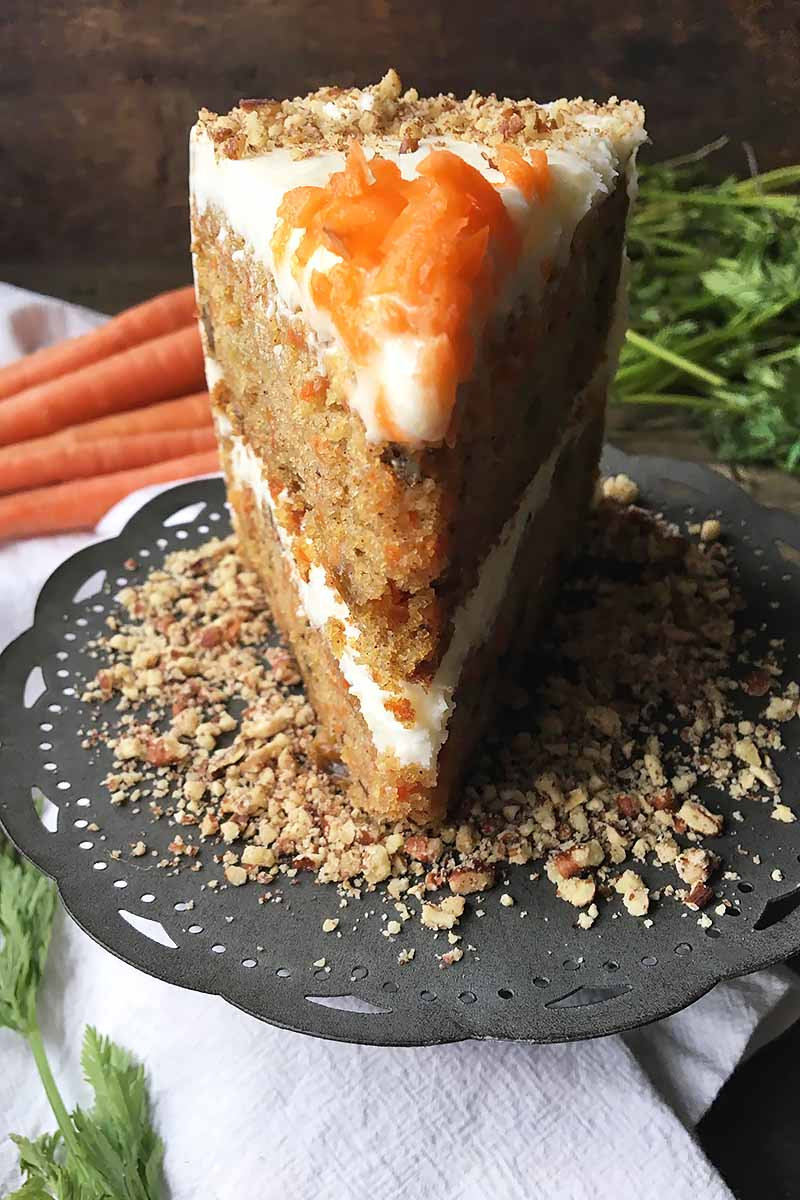 Vertical image of a slice of carrot cake on a bed of ground nuts on a dark plate with fresh vegetables in the background.