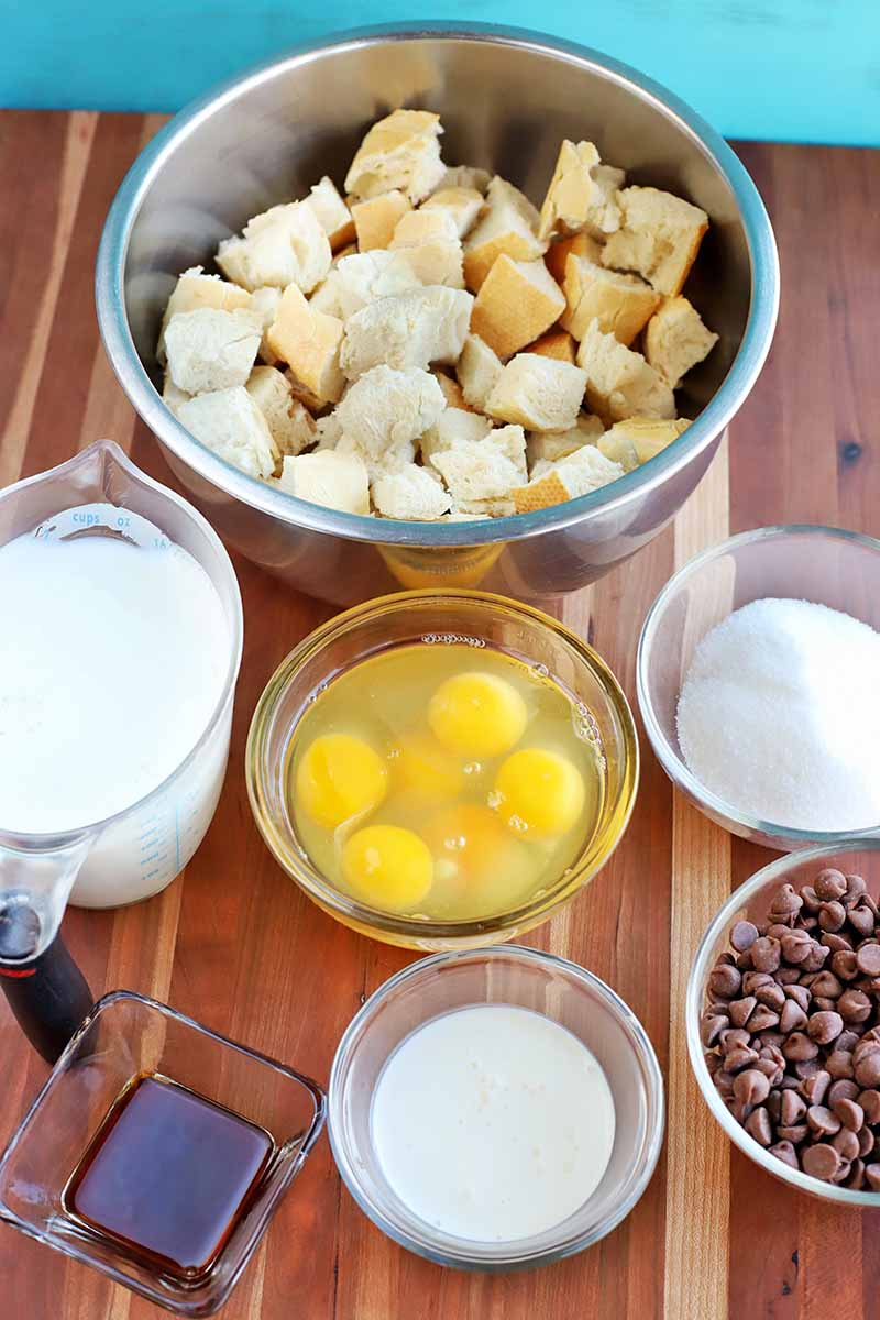 Vertical oblique overhead shot of a stainless steel bowl of bread cubes, a plastic measuring pitcher of milk, and glass bowls of cracked eggs, sugar, chocolate chips, cream, and vanilla extract, on a striped beige and brown wood surface with a robin's egg blue background.