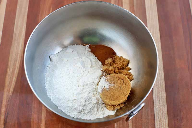 Overhead shot of a stainless steel mixing bowl with ring handle, with flour, packed brown sugar, and cinnamon at the bottom, on a wood surface.