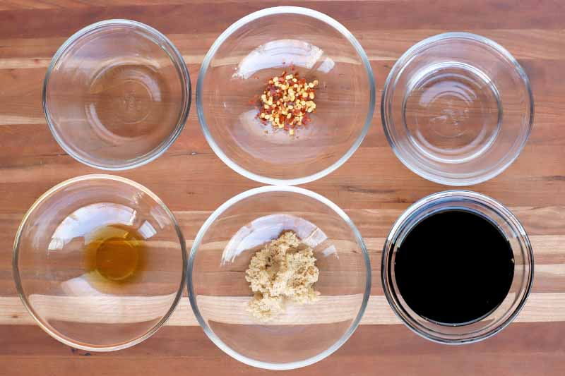Overhead horizontal shot of six small glass bowls of oil, vinegar, chili flakes, garlic, and soy sauce, on a light brown wood surface.