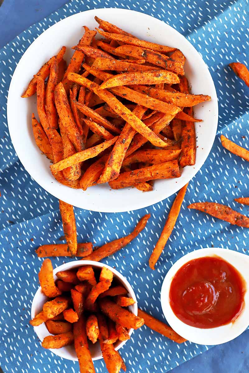 Vertical top-down image of a dish of sweet potato fries and ketchup on a blue napkin.