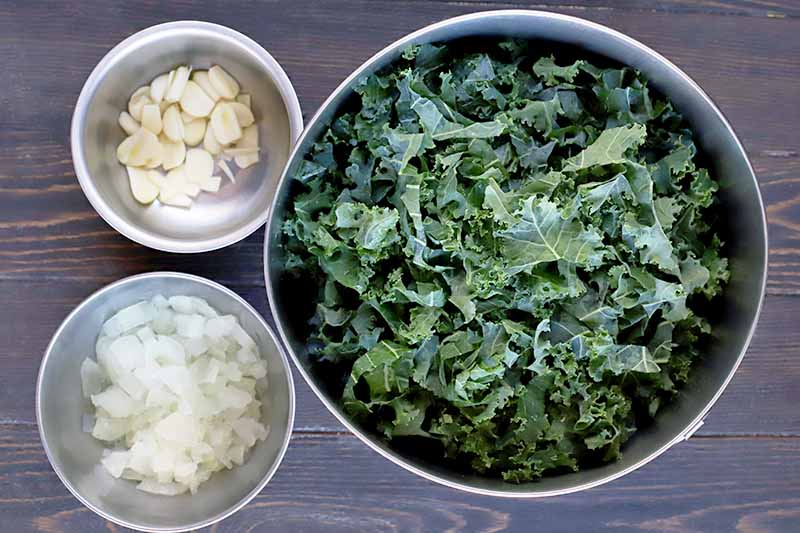 Overhead shot of a stainless steel bowl of torn uncooked curly leaf kale, and two smaller bowls to the left containing sliced cloves of peeled garlic and chopped onion, on a dark brown wood surface.