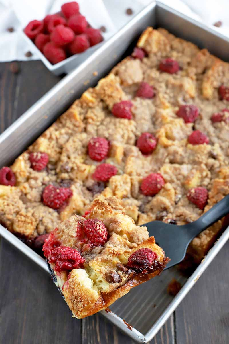 Oblique overhead vertical shot of a metal baking pan of homemade French toast casserole, with a portion being held up to the camera on a black plastic spatula, on a dark brown wood surface with a small, square, ceramic dish of fresh raspberries in the background.