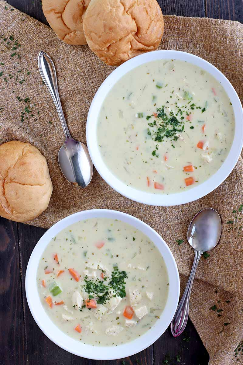 Overhead vertical shot of two white bowls of homemade cream of mushroom soup with fresh vegetables and herbs, with three kaiser rolls, two spoons, and scattered chopped parsley on a dark brown wood surface topped with a light brown piece of burlap.