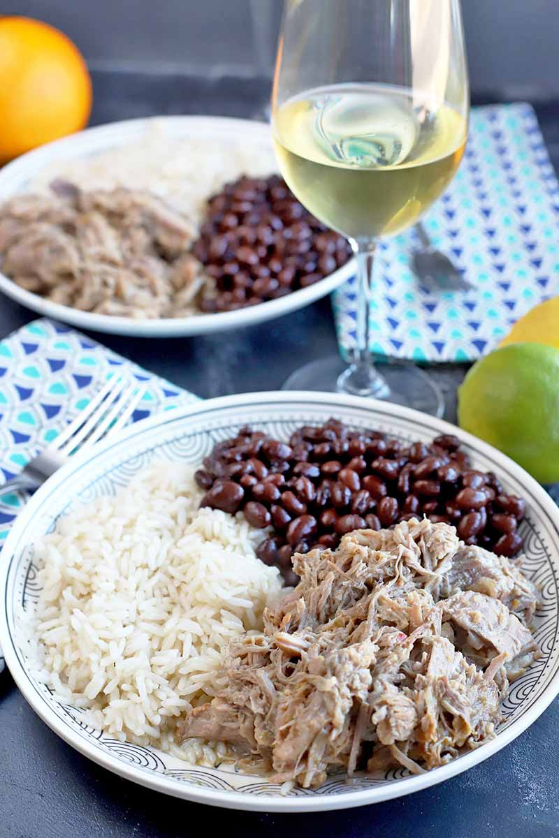 Vertical image of two plates with pork, black beans, and white rice next to blue napkins, forks, and a wine glass with white wine.