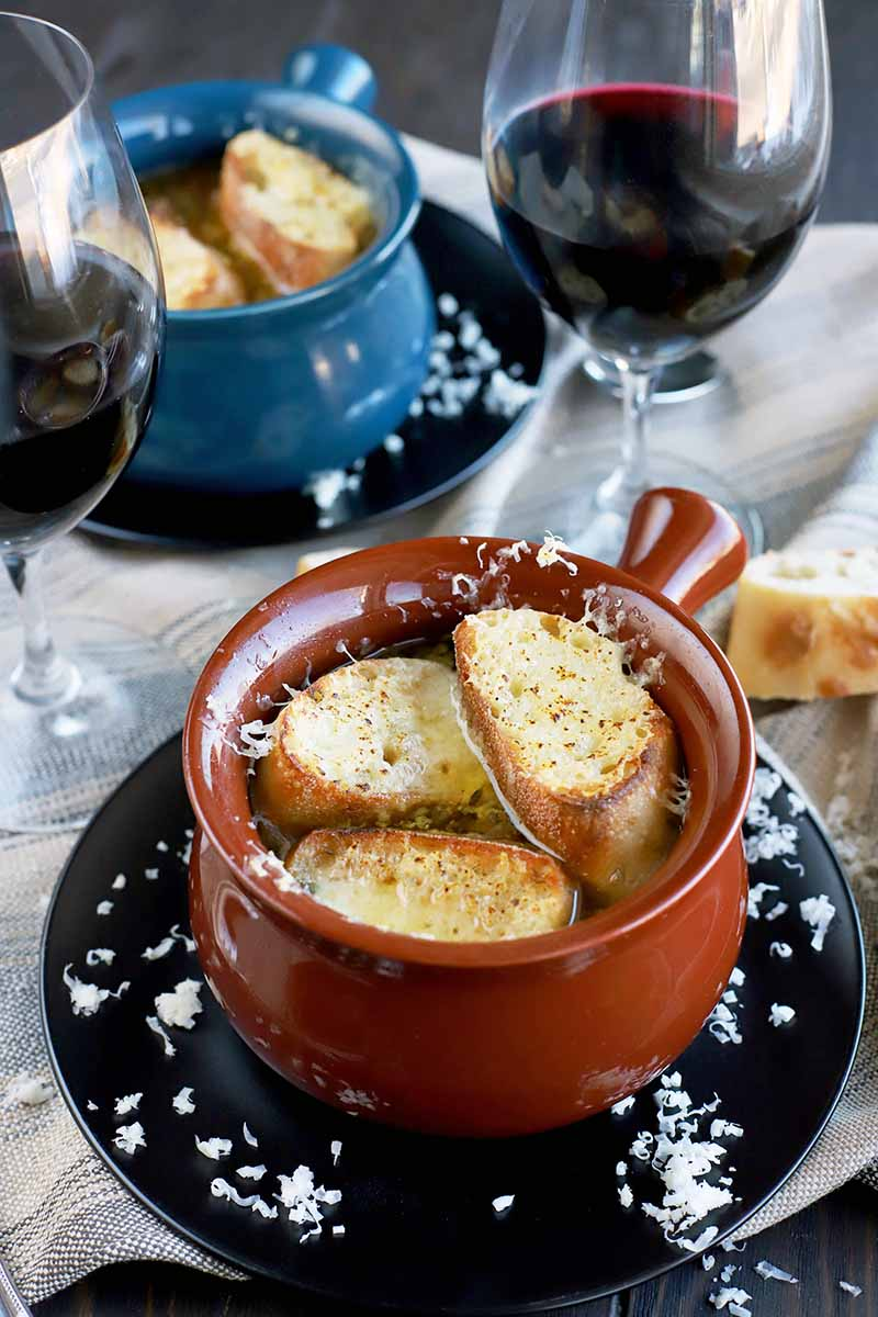 Vertical image of one blue and one brown ceramic crock filled with homemade French onion soup topped with toasted baguette slices and melted cheese, with scattered grated Swiss on two black plates, with two glasses of red wine and scattered baguette rounds on a gray striped cloth.