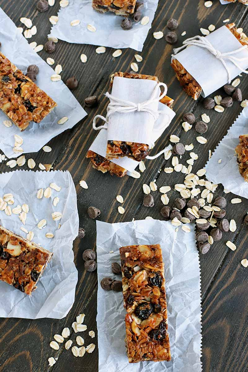Overhead vertical shot of rectangular homemade granola bars on pieces of parchment paper, with a short stack in the middle of bars wrapped in paper and tied with white cooking string, on a dark brown wood table with scattered uncooked oats.