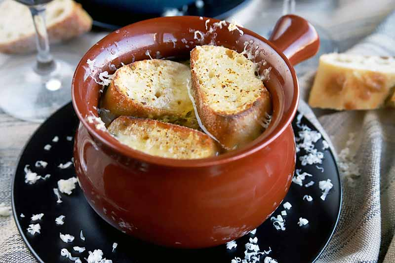 Closeup of a brown glazed ceramic crock of French onion soup topped with toasted baguette slices and melted cheese, on a black plate with scattered bits of grated Swiss, on a gray cloth with bread and a wine glass.