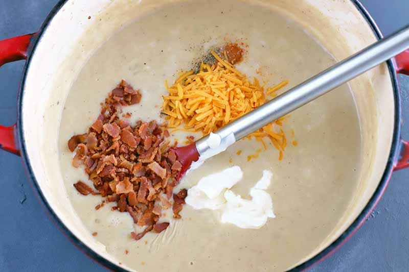 A large red and cream-colored enameled cooking pot filled with potato soup with piles of crumbled bacon and shredded cheddar cheese and a dollop of sour cream on top, about to be stirred in with a silver-handled spoon, on a gray slate surface.