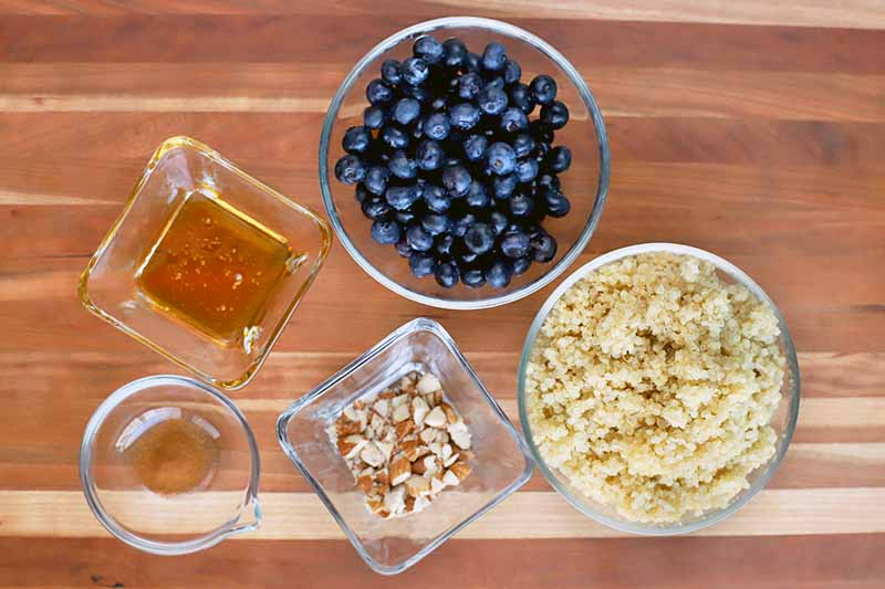 Overhead shot of three medium round, two small square, and one small round glass bowls on a brown and beige wood surface, filled with fresh blueberries, cooked quinoa, chopped almonds, honey, and cinnamon.