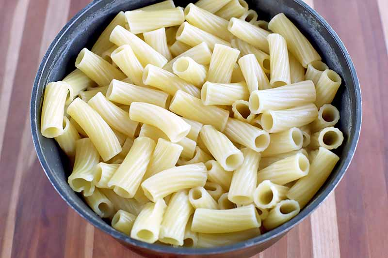 Overhead horizontal shot of a pot of cooked rigatoni, on a light brown and beige wood surface with vertical stripes.