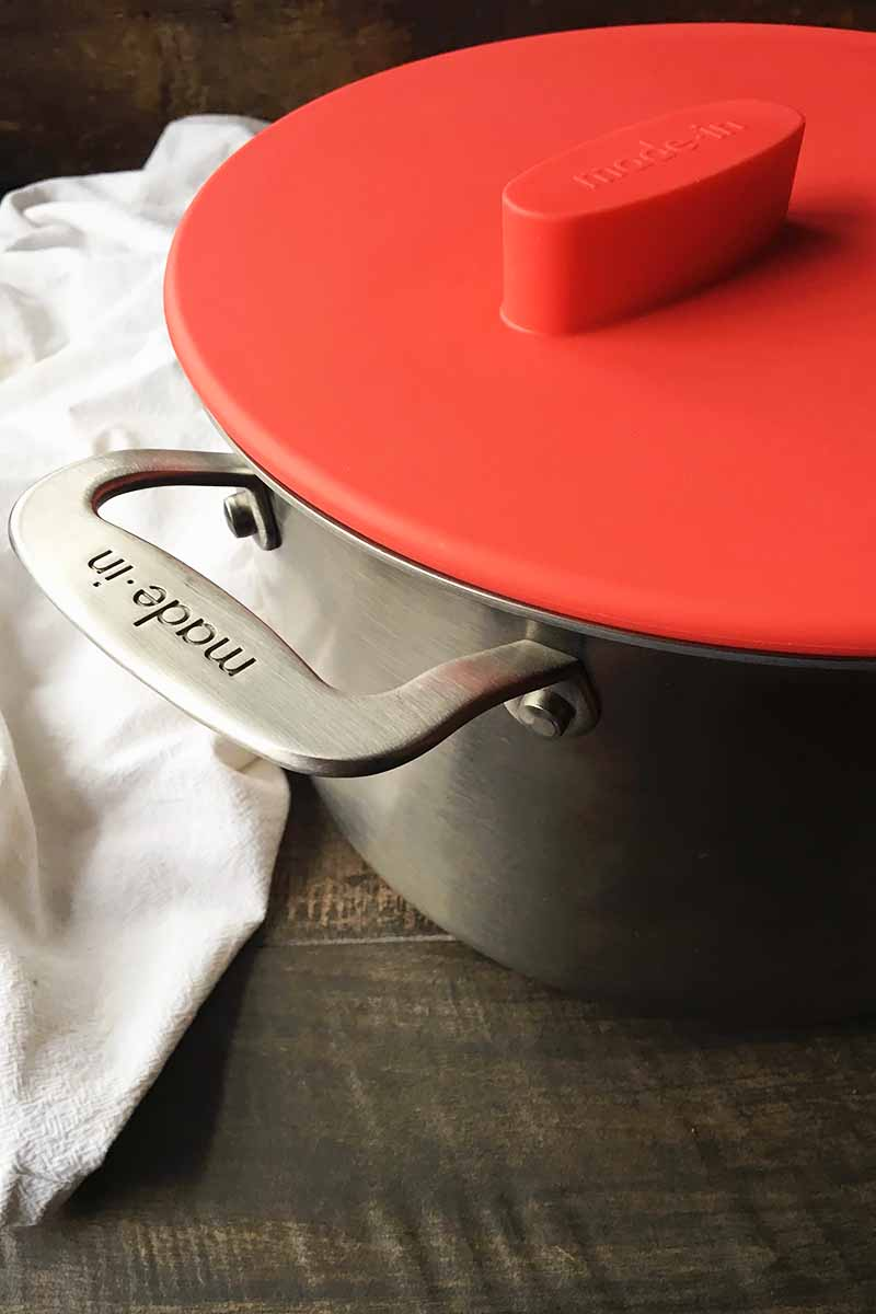 Vertical image of a metal pot and a lid on top, both with the Made In brand, next to a white towel.