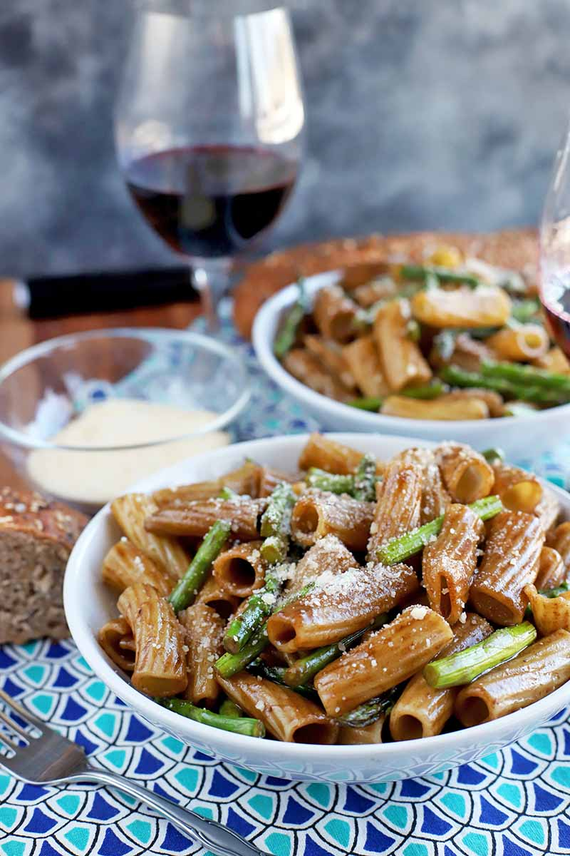 Vertical head-on image of two shallow white ceramic bowls of pasta with asparagus and a brown sauce, with a small glass bowl of grated Parmesan and a glass of red wine, on a dark and light blue cloth place mat on a brown wood table, with a mottled gray background.