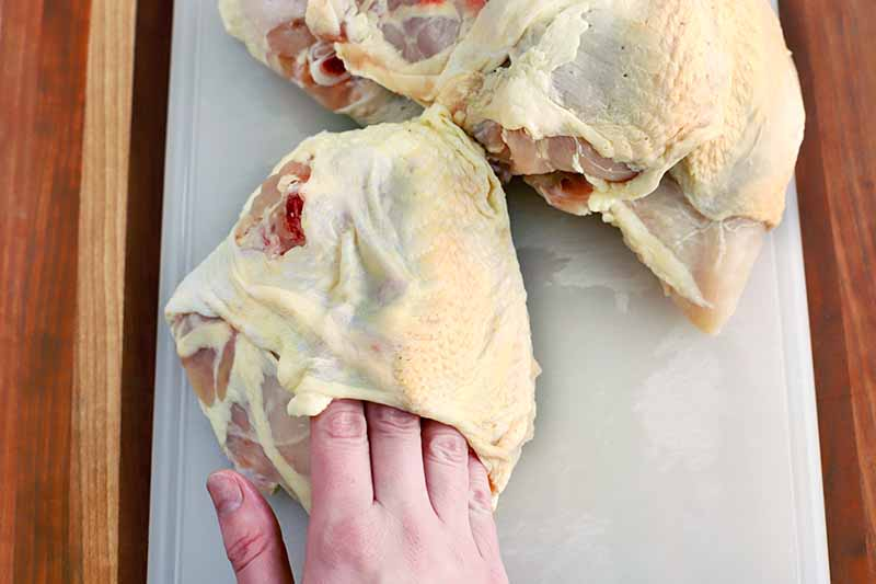 Four fingers of a hand are inserted under the skin of a bone-in chicken breast to release it partially from the meat, on a white cutting board with more poultry pieces, on a wood surface.
