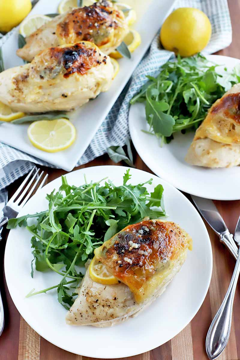 Vertical oblique shot of two white plates of roast skin-on chicken breast with arugula salad, a serving platter of more poultry with thin citrus slices for garnish, and two lemons on a folded and gathered blue and white cloth, on a wood table with stainless steel silverware.