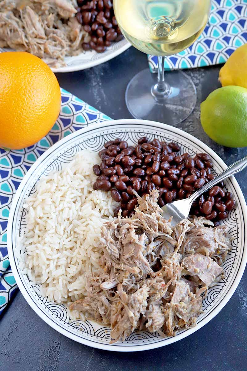 Vertical image of a fork picking up pulled pork on a plate of rice and beans.