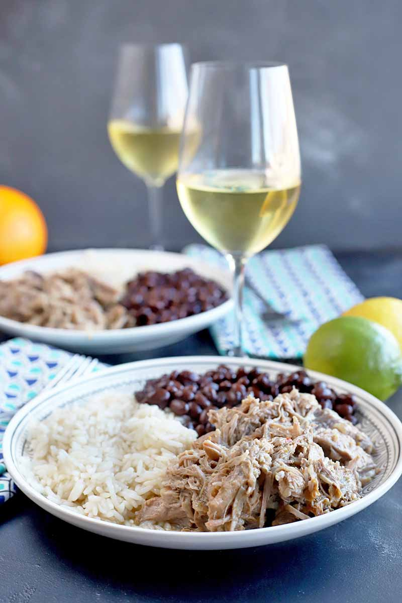 Vertical image of two plates with meat, rice, and beans with citrus and wine glasses with white wine