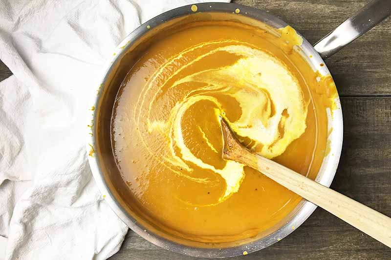 Horizontal image of heavy cream stirred into an orange liquid in a pot.