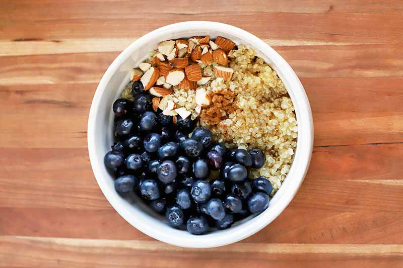 Overhead horizontal shot of a white bowl of cooked quinoa, fresh blueberries, chopped almonds, and cinnamon, on a brown and beige wood surface.