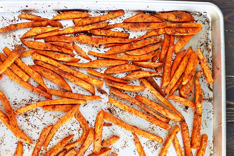 Horizontal image of baked spiced sweet potato strips.