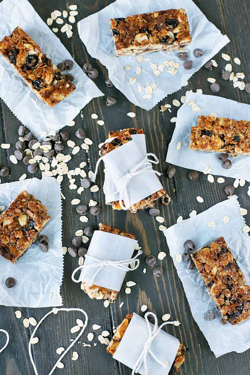 Overhead vertical shot of homemade granola bars, on rectangles of roughly cut white parchment paper or tied with parchment and white cooking string, on a dark brown wood surface with a piece of string and scattered uncooked oats.
