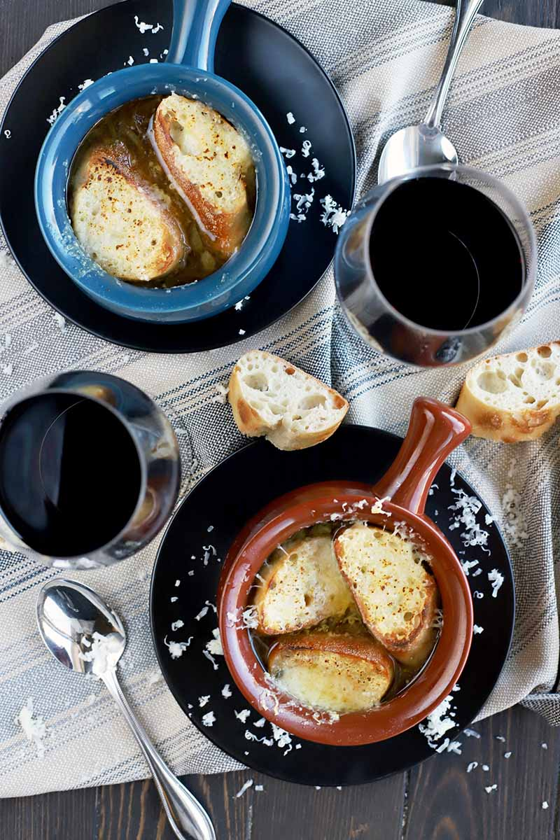 Overhead vertical image of one blue and one brown ceramic crock with French onion soup, toast, and melted cheese inside, on black plated with scattered grated Gruyere, two glasses of red wine, two spoons, and sliced baguette, on a gray striped cloth spread on top of a dark brown wood table.