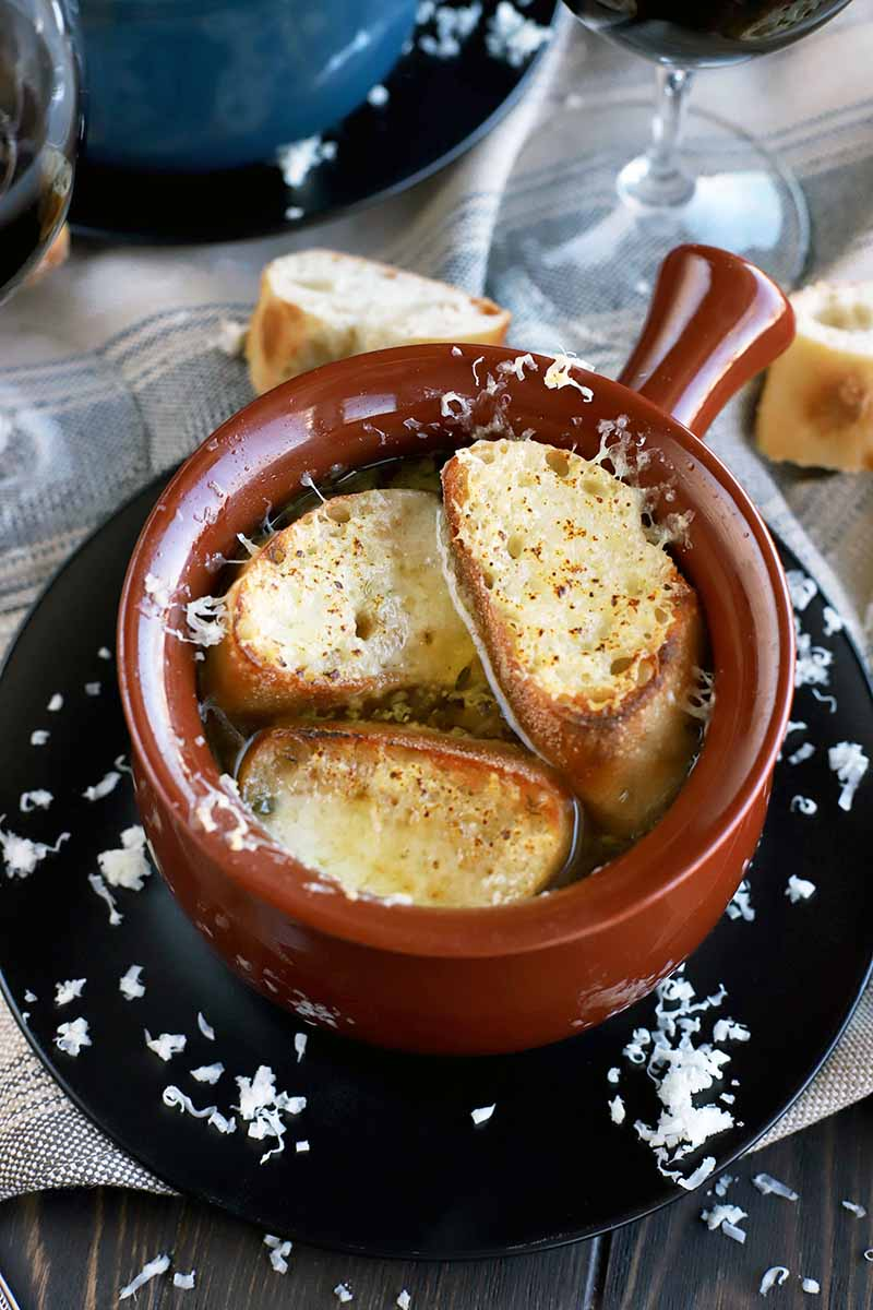 Vertical oblique shot of a glazed brown ceramic crock with a handle on a black plate, filled with French onion soup topped with melted cheese and toast, with scattered grated Swiss and baguette slices on a gray cloth on top of a dark brown table, with a blue crock and a glass of red wine in the background.