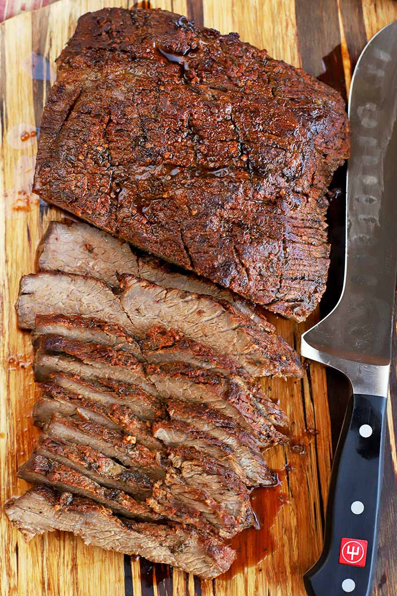 Overhead shot of slices and a remaining uncut portion of roasted beef brisket, on a wooden cutting board with a carving knife.