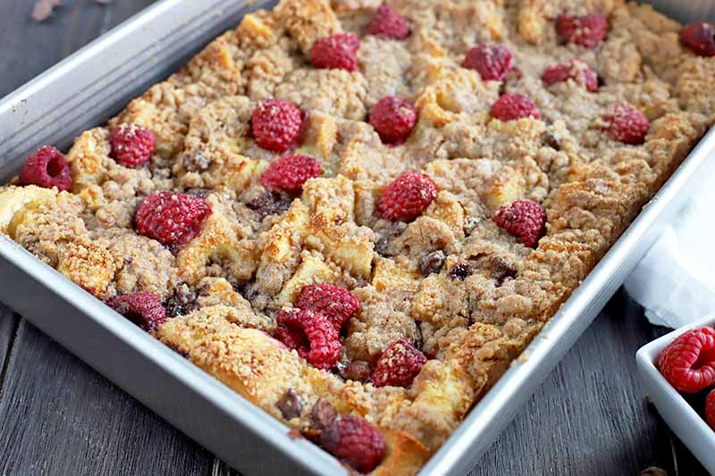 Horizontal image of a raspberry and chocolate French toast casserole with brown sugar crumble topping in a metal baking pan arranged at an oblique angle, with a small, white, square ceramic dish of fresh berries just visible at the bottom right, on a dark brown wood surface.